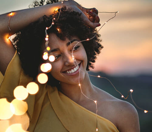 Boost your Confidence: Overcome Fear and Anxiety to Step into Life - Woman smiling confidently while holding a string of lights, RebeccaRoberts.com